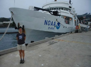 NOAA Teacher at Sea, Elizabeth Eubanks, standing in front of the majestic NOAA ship DAVID STARR JORDAN in the San Diego Harbor.