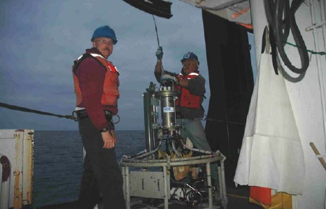 NOAA scientists, Eric Lynn and Dr. Russ Vetter prepare to lower the CTD. Notice the green cylinders on the left side of the CTD – they are bottles for water samples.