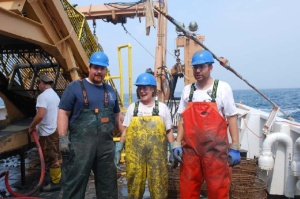 Laurie and some fellow crewmembers are covered with clay and mud after climbing in the dredge
