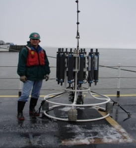 NOAA Teacher at Sea, Scott Donnelly, next to a CTD with Niskin bottles in port at Astoria, OR