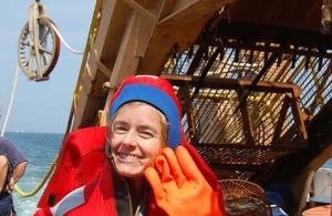 NOAA Teacher at Sea, Lisbeth Uribe, in her survival suit next to the dredge