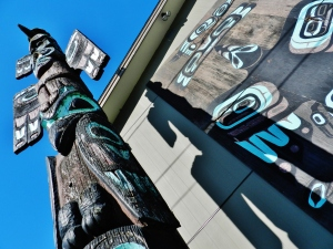 Tlingit totem pole and wall painting on Village Drive in Juneau