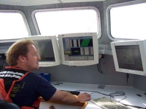 Surveyor Doug Wood observes computer screens where data is being collected. The green triangle is showing multi-beam sonar data.