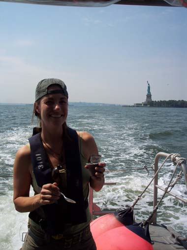 NOAA Teacher at Sea, Candice Autry, enjoys pudding while taking a break from observing data collection using side-scan sonar. The Statue of Liberty is in the background!