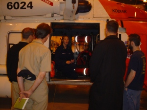 The FAIRWEATHER officers listen to a briefing about the helicopter rescue drill planned for later in the day.
