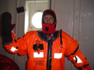 """Teacher at Sea Dave Babich trying on the survival (or """"Gumby"""") suit during an abandon ship drill."""