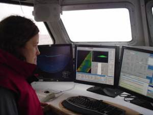 Physical Scientist Martha Herzog monitors data being received from the survey launch's sonar.