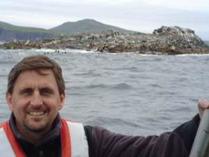 Teacher at Sea Dave Babich sits on Survey launch with Steller Sea Lions in background.