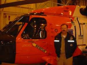 Commander Beaver stands next to a coast guard rescue helicopter at their base in Kodiak, Alaska.