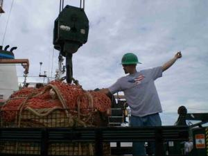 Lead fisherman Pete Langlois helping load cargo that will be used Leg 1 of a Hydroacoustic Survey.