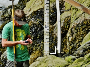 HAST Curran McBride collecting data near the tide staff
