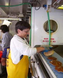 NOAA Teacher at Sea, Patti Connor, helps to sort sea scallops aboard NOAA ship ALBATROSS IV.