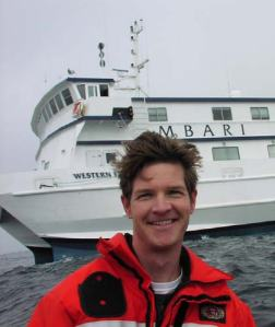 NOAA Teacher at Sea Noah Doughty with the Monterey Bay Aquarium Research Institute (MBARI) R/V WESTERN FLYER in the background.