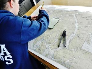 Ensign Micki Ream plotting a course on the bridge