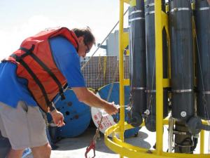 Dr. Lukas, aboard the REVELLE collecting water samples from the CTD.