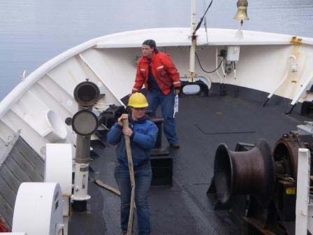 Able Seaman Leslie Abramson in background and Jodie Edmond in foreground preparing to raise the anchor