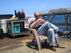 "Dr. Kurt Collins listening to the ball game on the ""Leedo deck"" off watch."