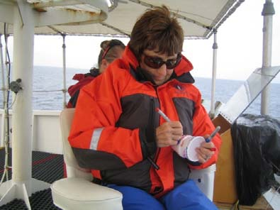 NOAA Teacher at Sea Elsa Stuber prepares a cup to be sent down to -4500 meters with the CTD.