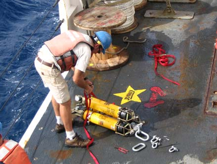 Here, a scientist is checking an acoustic release mechanism.  They lowered it to 1,500 m or approximately 4,500 feet to test it. It will eventually be located 4,000 m beneath the surface or approximately 12,000 ft!