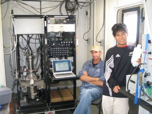 Dr. Byron Blomquist (seated) and graduate student Mingxi Yang (standing) beside the Atmospheric Pressure Ionization Mass Spectrometer or APIMS.