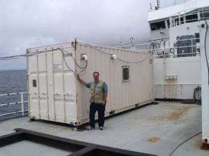 Mr. Hoyt standing in front of Dr. Blomquist's portable lab.  Please note the wires leaving the lab to the left of the photo.