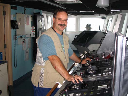 """Mr. Hoyt """"driving"""" the ship.  The two controls I am holding are how the ship is steered. The ship has no rudder and the pilot need only to rotate these controls to turn the propellers in a different direction. Much like turning the motor on a small boat."""