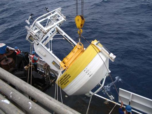 Lifting the Stratus 7 Buoy off the ship.  This process takes the cooperation of about a dozen individuals to do.