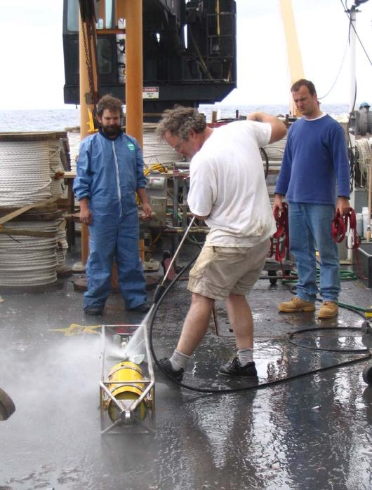 """Dr. Weller, leading by example, cleaning the equipment free of barnacles.  Remember in an earlier posting when he stated he was a """"hands on scientist""""?"""