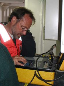 Jeff Lord using an acoustic transmitter to talk to the acoustic release.  This machine also tells the scientists the range to the release that helps them in finding it.