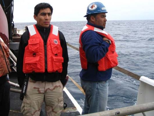 Jorge Araya and Alvaro Vera, members of the Chilean Navy, looking for the yellow glass balls which were released over an hour ago and take that long to reach the surface.  Work vests were required but not hard hats for this part of the operation.  Both have over 12 years with the Chilean Navy.