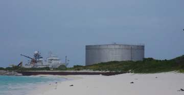 NOAA Ship OSCAR ELTON SETTE seems to be dwarfed by one of the huge fuel tanks on Sand Island at Midway Atoll.