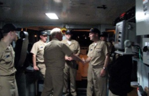 Rear Admiral De Bow handing the Command Coin to Commander Noll