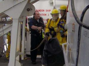 Executive Officer Sean Cimiculla oversees the operations of an on-board firedrill. The sailing crew trains regularly for fire scenarios on the ship.