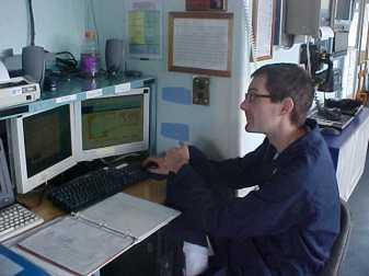 Photo of ENS Nathan Eldridge logging weather data from the  RAINIER to be sent into NOAA for weather analysis of the area.