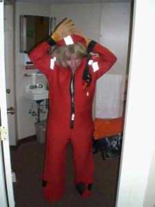 "Nancy McClintock, NOAA Teacher at Sea, tries on a survival suit informally known as a ""Gumby Suit."" The suit helps to prevent hypothermia in case there is an emergency requiring evacuation of the ship."