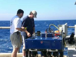Kevin Joy and Craig Bussel, ROV crew navigator  and pilot, install one of the cameras in preparation  for ROV deployment.