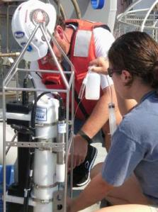 Marta Ribera and Andy David, NOAA scientists, prepare the CTD for deployment.  The CTD recorded conductivity, temperature, and depth of the ocean on this cruise.