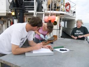 Mike recording data as Lead Scientist Kristen Hannan dissects a Gulper Shark from a previous survey.