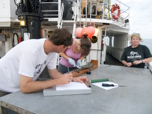 Mike recording data as Lead Scientist Kristen Hannan dissects a Gulper Shark from a previous survey.