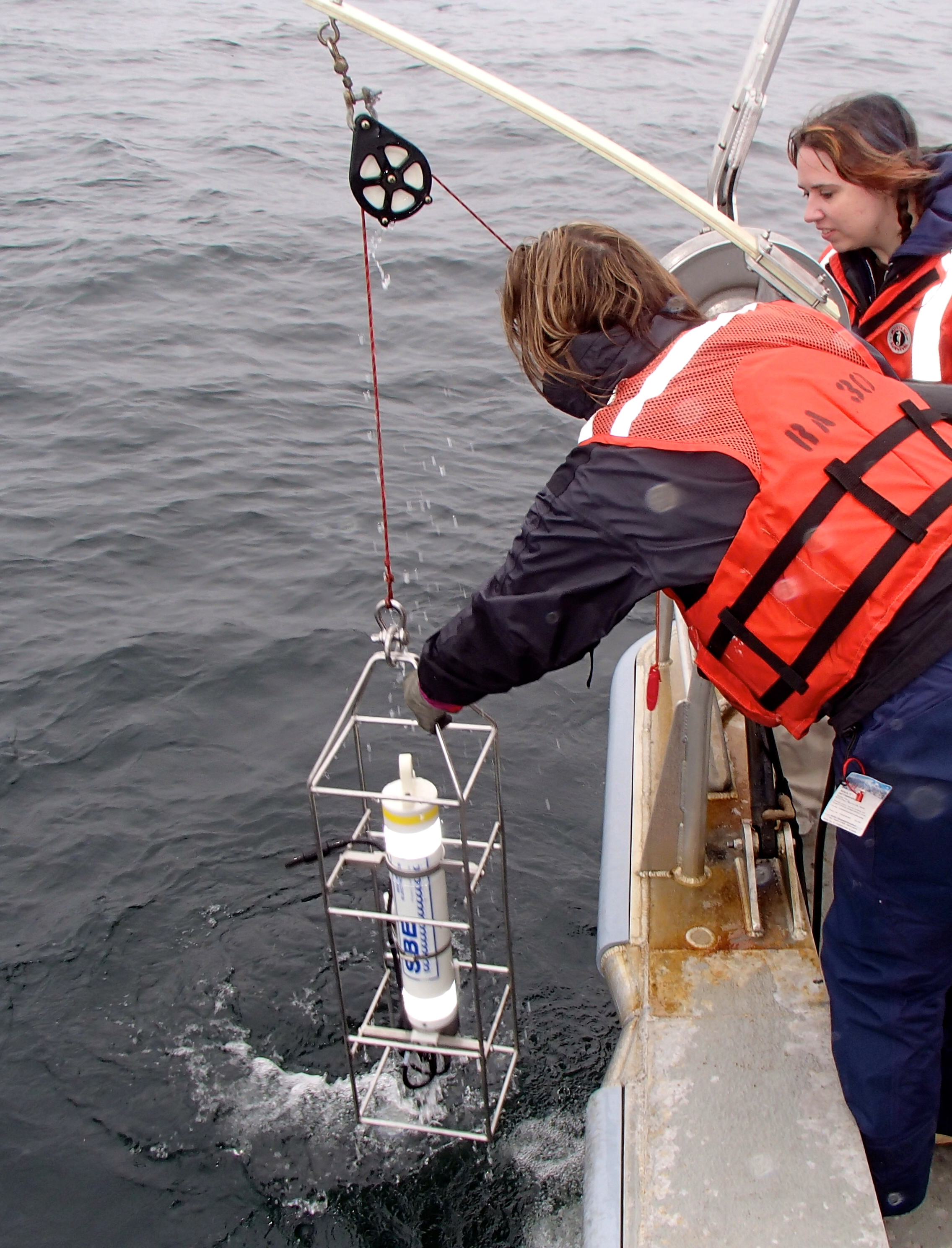 """Avery lowers the CTD into the water for a """"cast"""". The CTD needs to sit in the water for a few minutes to acclimate before being lowered for a profile."""