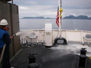 CB Kruger demonstrating fire suppression foam on the fantail of the RAINIER.