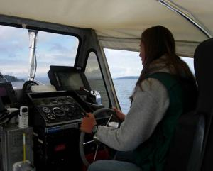 Having her hand at the wheel, TAS Jessica Schwarz steers launch boat, RA4 during a productive day of hydrographic surveying.