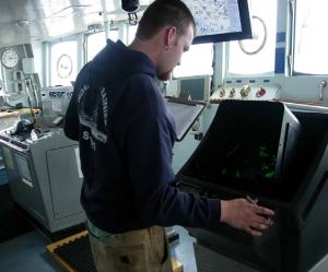 On the bridge, Vessel Assistant, Kelson Baird is logging the ships position from four points on the radar screen.  The position of the points is recorded every half hour to monitor the effectiveness of the anchor.