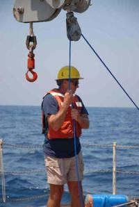 Steve Matthews, fisheries methods and equipment specialist, coordinates crane operations during deployment of the 4-camera array.