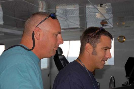 From left, Allan Gravina, Able Bodied Seaman, and Mike filled 3 and ½ pages.  The Nicholas, 2nd Mate, on the bridge during the  0800-1200 bridge watch.  Their duties while on watch include monitoring the ships position in relation to other vessels, land, and obstacles, piloting the vessel and monitoring the ships systems and accurate quotes and used notes.  communications.  They're ability to pilot the ship was crucial to the success of the ROV dives.  When not on watch they frequently lend a hand on deck.   Off duty both of them enjoy fishing or a good game of Spades.
