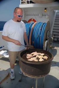 """Patrick """"Cookie"""" Downey grills up some freshly caught dolphin fish."""