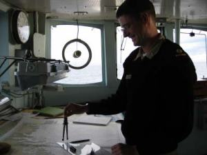 ENS Sam Greenaway works on a nautical chart.