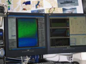 Computer showing data being acquired from the RAINIER ship sonar.  The blue color means deeper water.  The green color is shallower water.
