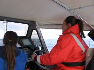 TAS Kim Wolke driving a survey boat with Able-Bodied Seaman Jodie Edmond looking on.