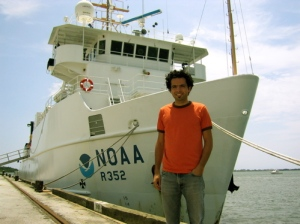 Thomas Nassif stands in front of the NOAA research vessel NANCY FOSTER.